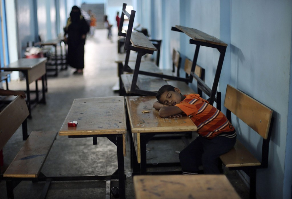 A Palestinian boy, who fled his family's house following an Israeli ground offensive, sleeps as he stays at a UN-run school in Rafah